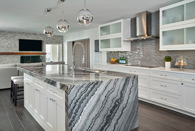 Kitchen remodel in Bonita Springs, FL with granite waterfall countertops, large island, and white shaker cabinets.